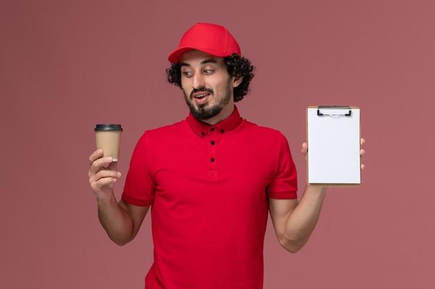 Vue avant de l'homme de livraison de messagerie homme en chemise rouge et cape tenant une tasse de café marron et bloc-notes sur le mur rose clair service de livraison uniforme employé