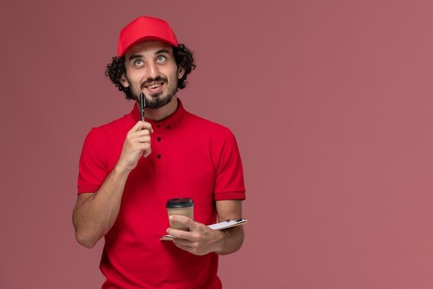 Vue avant de l'homme de livraison de messagerie homme en chemise rouge et cape tenant une tasse de café marron et bloc-notes pensant sur le mur rose employé de livraison uniforme de service