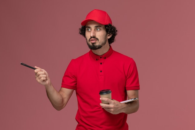 Vue avant de l'homme de livraison de messagerie homme en chemise rouge et cape tenant une tasse de café marron et bloc-notes avec stylo sur mur rose clair emploi employé de livraison de services