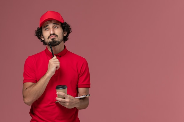 Vue avant de l'homme de livraison de messagerie homme en chemise rouge et cape tenant une tasse de café marron et bloc-notes avec un stylo pensant sur le travail d'employé de livraison de services mur rose clair