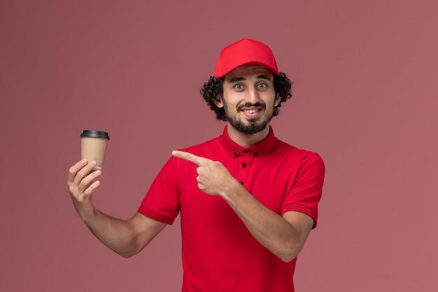 Vue avant de l'homme de livraison de messagerie homme en chemise rouge et cape tenant une tasse de café marron sur un mur rose clair employé de livraison uniforme de service mâle
