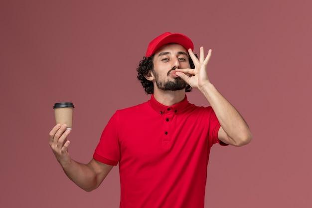Vue avant de l'homme de livraison de messagerie homme en chemise rouge et cape tenant une tasse de café marron sur le mur rose clair employé de livraison uniforme de service
