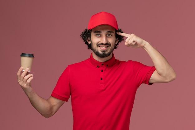 Vue avant de l'homme de livraison de messagerie homme en chemise rouge et cape tenant une tasse de café marron sur un mur rose clair service de livraison uniforme employé de travail masculin