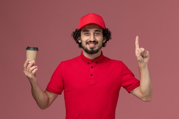 Vue avant de l'homme de livraison de messagerie homme en chemise rouge et cape tenant une tasse de café marron sur un mur rose clair service de livraison uniforme employé travailleur