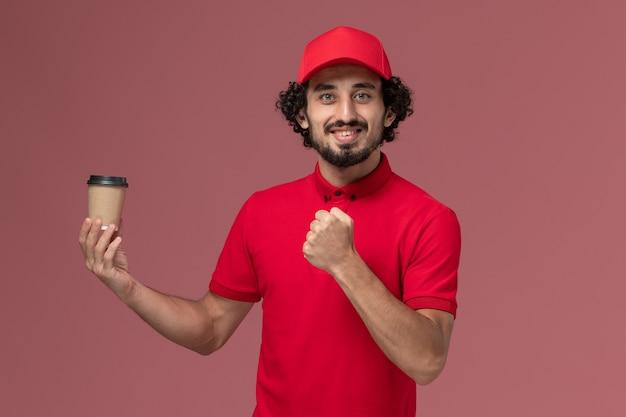 Vue avant de l'homme de livraison de messagerie homme en chemise rouge et cape tenant une tasse de café marron sur le mur rose service de livraison uniforme employé homme emploi