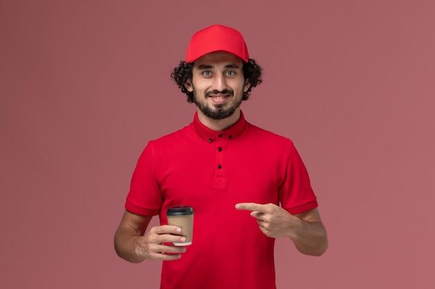 Vue avant de l'homme de livraison de messagerie homme en chemise rouge et cape tenant une tasse de café marron sur le mur rose service de livraison uniforme employé travail masculin