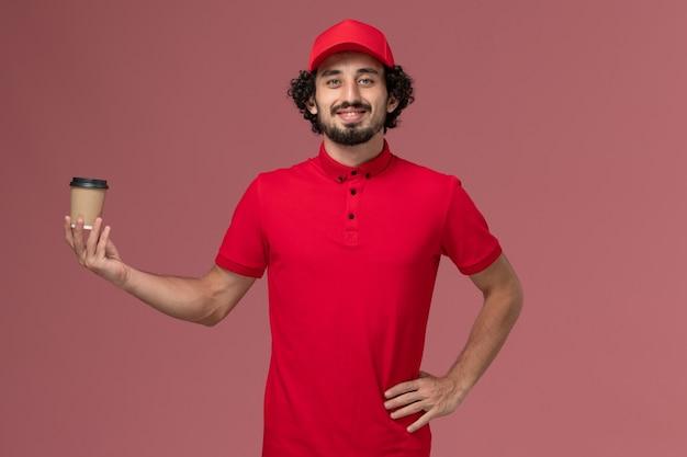 Vue avant de l'homme de livraison de messagerie homme en chemise rouge et cape tenant une tasse de café marron sur le mur rose service de livraison uniforme employé travail travailleur masculin