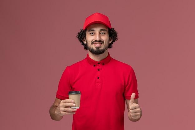 Vue avant de l'homme de livraison de messagerie homme en chemise rouge et cape tenant une tasse de café marron sur le mur rose service de livraison uniforme employé travail travailleur travail