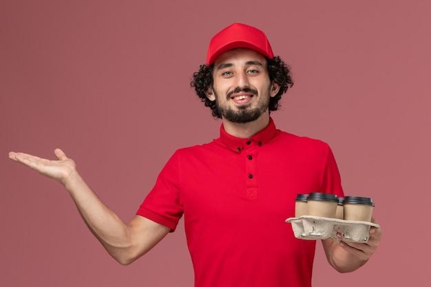 Vue avant de l'homme de livraison de messagerie homme en chemise rouge et cape tenant des tasses de café de livraison marron sur le mur rose clair employé de livraison de services masculins