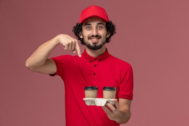 Vue avant de l'homme de livraison de messagerie homme en chemise rouge et cape tenant des tasses de café de livraison marron sur mur rose service de livraison employé travailleur emploi