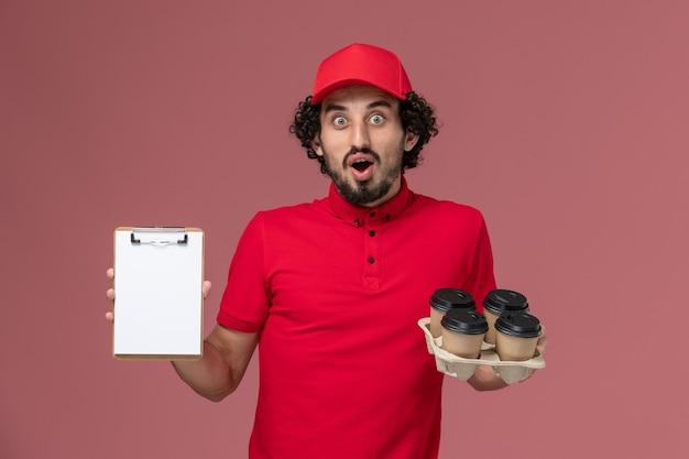 Vue avant de l'homme de livraison de messagerie homme en chemise rouge et cape tenant des tasses à café de livraison marron avec petit bloc-notes sur le mur rose travail des employés de livraison de services
