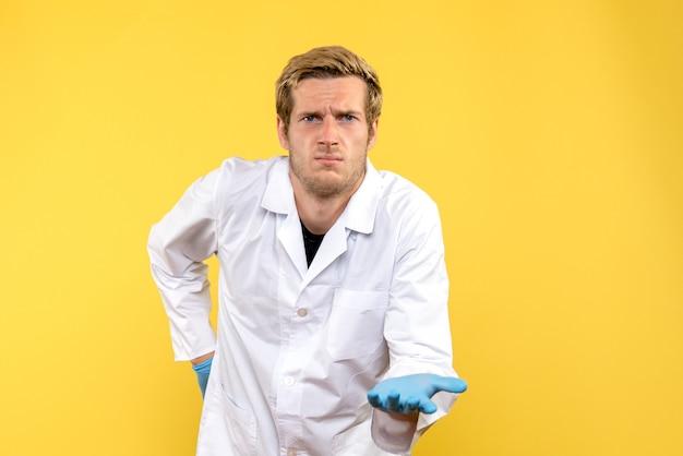 Vue avant de l'homme médecin confus sur le bureau jaune covid- émotion médicale humaine