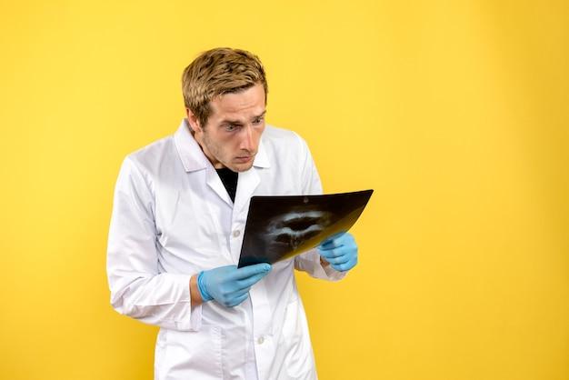 Vue avant de l'homme médecin contrôle crâne x-ray sur fond jaune chirurgie médicale covid-