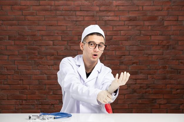 Vue avant de l'homme médecin en costume médical blanc derrière le bureau