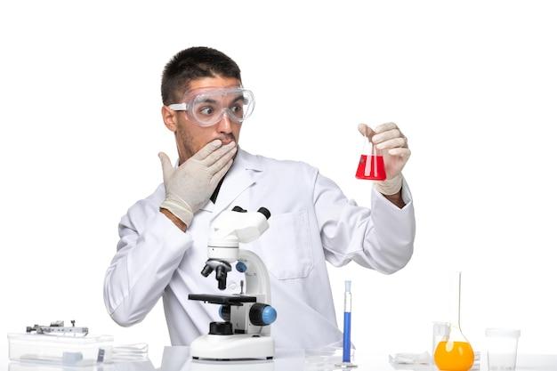 Vue avant de l'homme médecin en costume médical blanc avec des lunettes de soleil de protection sur un bureau blanc