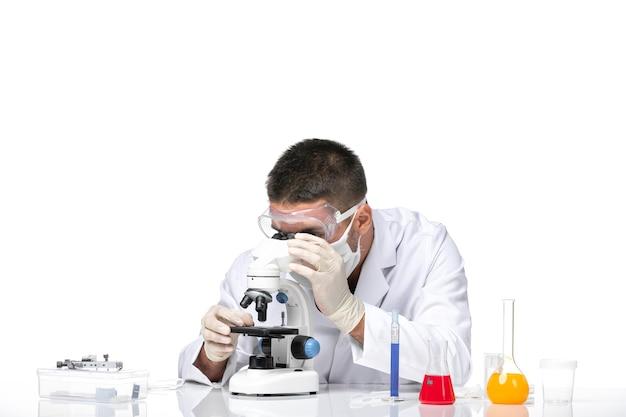 Vue avant de l'homme médecin en costume médical blanc avec masque en raison de covid à l'aide d'un microscope sur un bureau blanc
