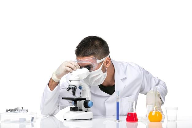 Vue avant de l'homme médecin en costume médical blanc avec masque en raison de covid à l'aide d'un microscope sur un espace blanc