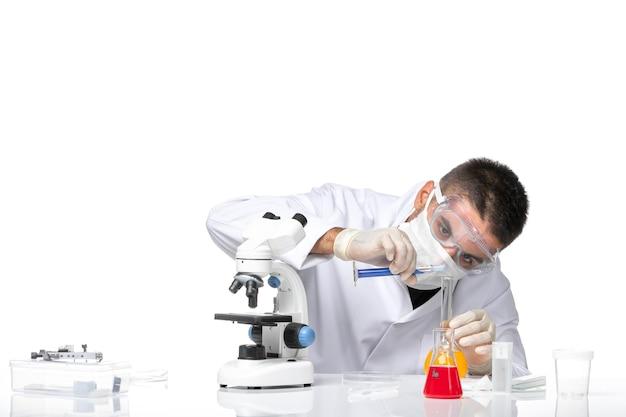 Vue avant de l'homme médecin en costume médical blanc avec masque en raison de covid travaillant avec des solutions sur un bureau blanc