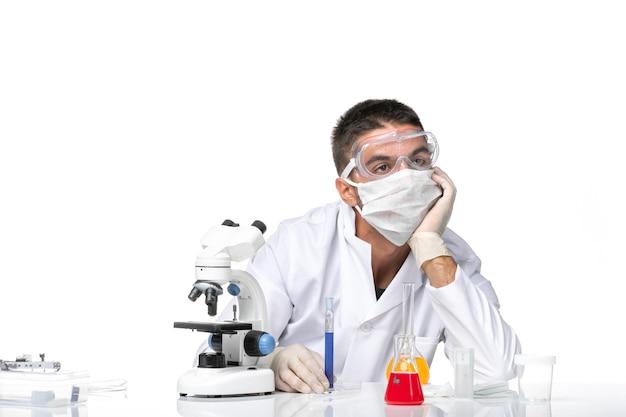 Vue avant de l'homme médecin en costume médical blanc avec masque en raison du travail de covid et a souligné sur l'espace blanc