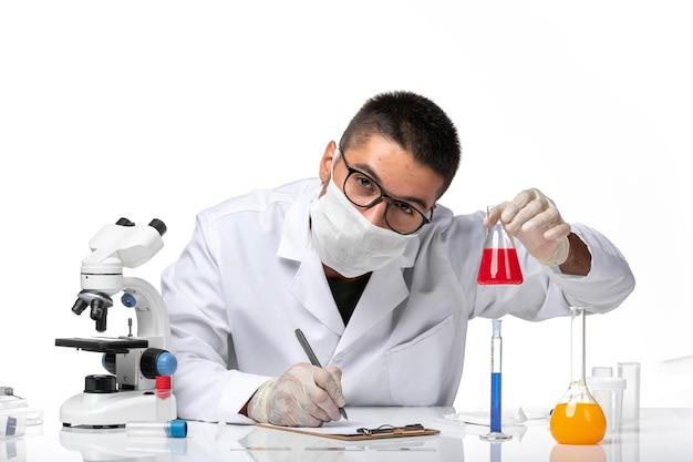 Vue avant de l'homme médecin en costume médical blanc et avec masque tenant une solution rouge sur un espace blanc clair