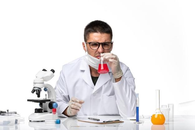 Vue avant de l'homme médecin en costume médical blanc et avec masque travaillant avec une solution sur un espace blanc clair