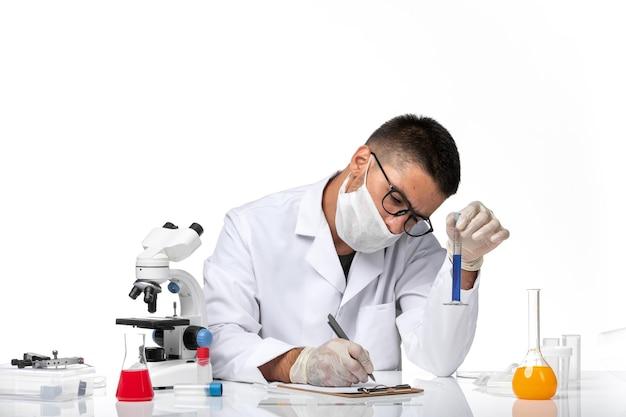 Vue avant de l'homme médecin en costume médical blanc et avec masque travaillant avec une solution sur un espace blanc