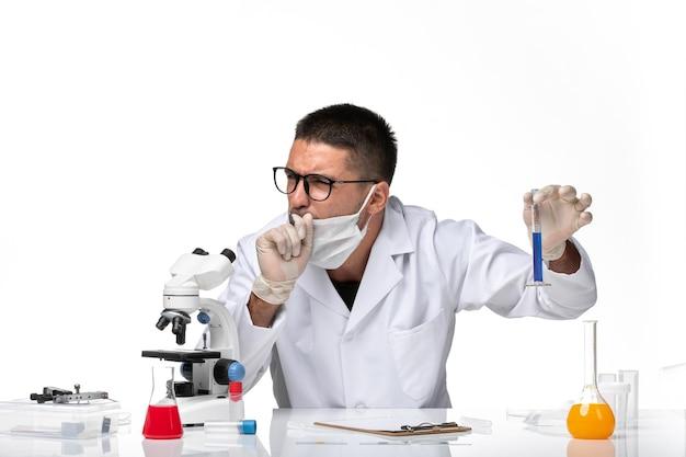 Vue avant de l'homme médecin en costume médical blanc et avec masque travaillant avec une solution de toux sur un espace blanc