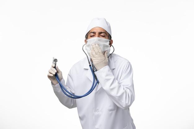 Vue avant de l'homme médecin en costume médical et masque en raison d'un coronavirus à l'aide d'un stéthoscope sur la surface blanche claire