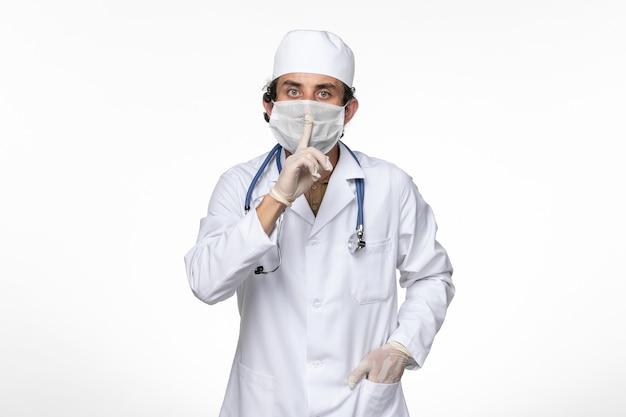 Vue avant de l'homme médecin en costume médical portant un masque stérile comme une protection contre la maladie du virus de la maladie pandémique covid