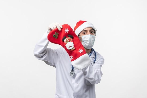Vue avant de l'homme médecin avec de grandes chaussettes de vacances sur le bureau blanc virus de noël covid