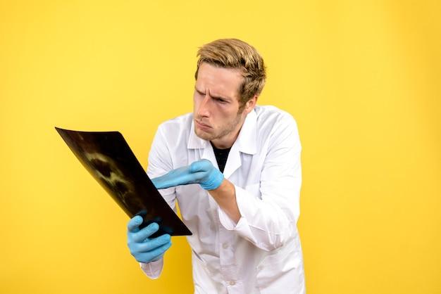 Vue avant de l'homme médecin holding x-ray sur fond jaune chirurgie medic covid hygiène