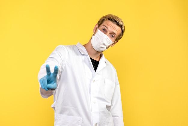 Vue avant de l'homme médecin montrant le signe de la victoire sur fond jaune virus pandémique covid- santé