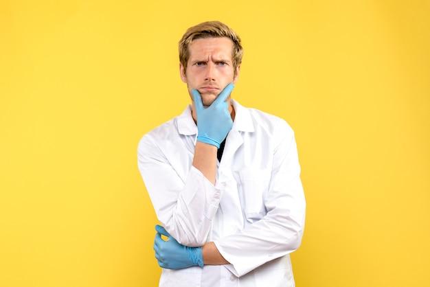 Vue avant de l'homme médecin pensant sur fond jaune clair humain medic covid- émotion
