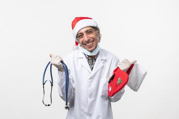 Vue avant de l'homme médecin souriant largement sur le virus du mur blanc covid vacances santé