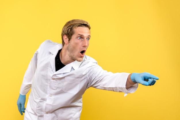 Vue avant de l'homme médecin surpris sur fond jaune medic covid- hôpital humain