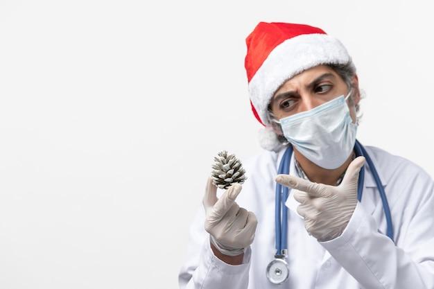 Vue avant de l'homme médecin tenant le cône sur le mur blanc virus santé covid-