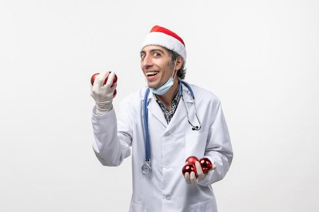 Vue avant de l'homme médecin tenant des jouets sur le mur blanc émotion de virus covid- santé