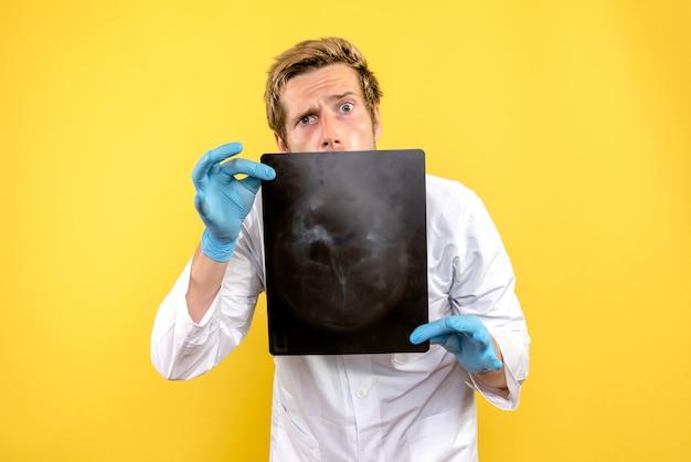 Vue avant de l'homme médecin tenant x-ray sur le bureau jaune chirurgie medic covid hygiène