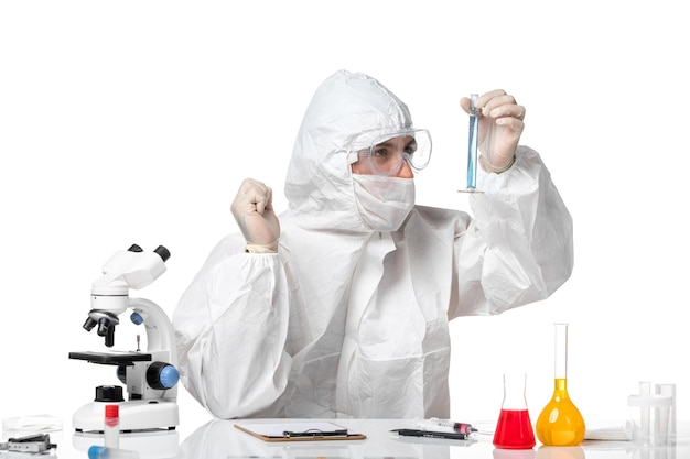 Vue avant de l'homme médecin en tenue de protection avec masque en raison de la fiole de maintien de covid avec une solution bleue sur l'espace blanc