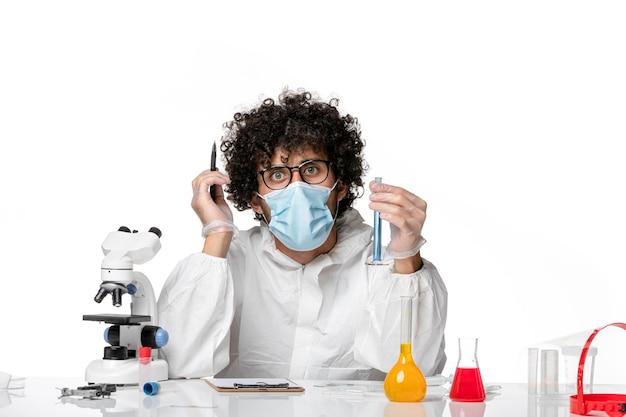 Vue avant de l'homme médecin en tenue de protection et masque tenant le flacon avec une solution bleue sur blanc 24 virus épidémique de la pandémie de covid pandémique