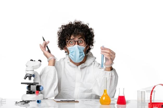 Vue avant de l'homme médecin en tenue de protection et masque tenant le flacon avec une solution bleue sur fond blanc clair pandemic covid- virus épidémique