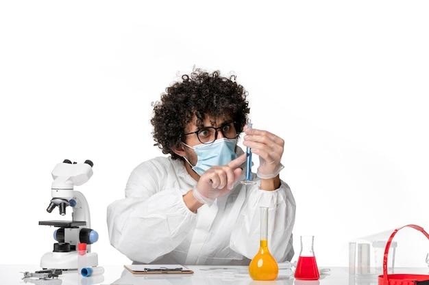 Vue avant de l'homme médecin en tenue de protection et masque tenant le flacon avec une solution bleue sur le fond blanc pandémique covid- virus épidémique
