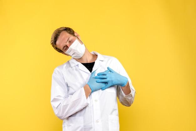 Vue avant de l'homme médecin touchant son cœur sur fond jaune pandémie de santé covid- medic