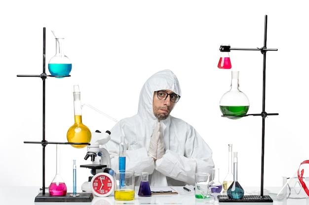 Vue avant de l'homme scientifique en combinaison de protection spéciale assis autour de la table avec des solutions