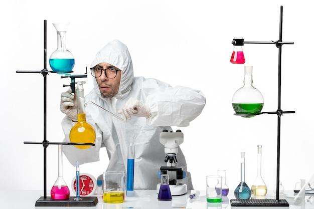 Vue avant de l'homme scientifique en combinaison de protection spéciale autour de la table avec des solutions