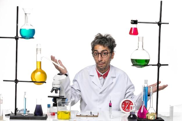 Vue avant de l'homme scientifique en costume médical assis en face de la table avec des solutions sur fond blanc chimie covid laboratoire virus santé