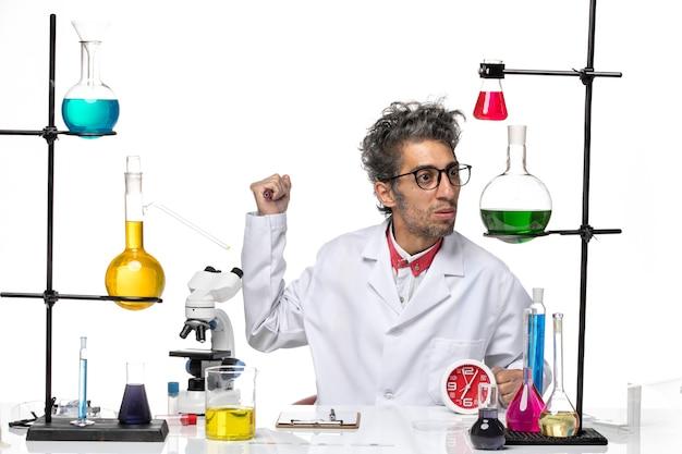 Vue avant de l'homme scientifique en costume médical assis en face de la table avec des solutions sur le fond blanc clair covid- laboratoire chimie de la santé des virus