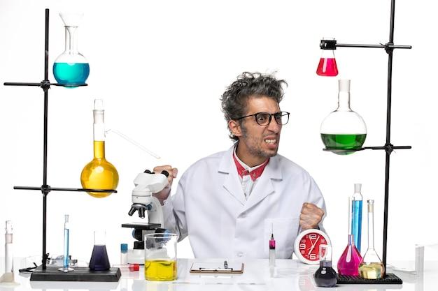 Vue avant de l'homme scientifique en costume médical assis en face de la table avec des solutions sur fond blanc virus laboratoire covid chimie de la santé