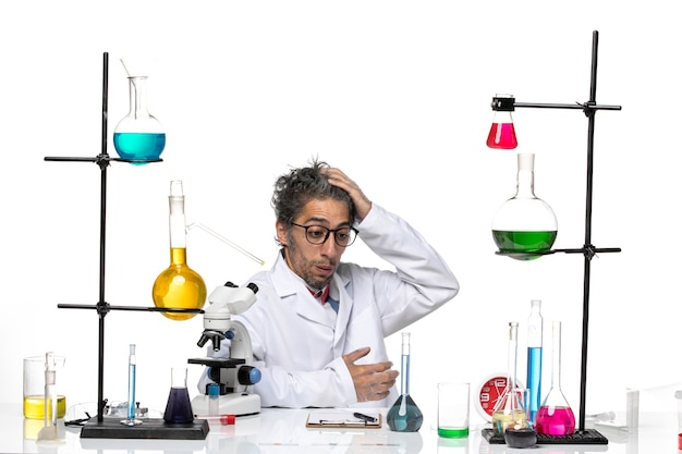 Vue avant de l'homme scientifique en costume médical blanc assis avec des solutions