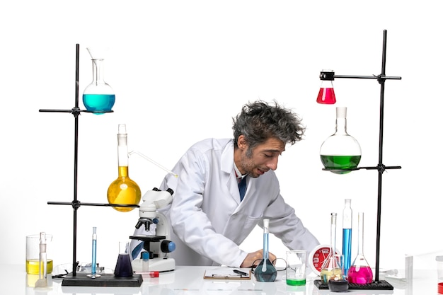 Vue avant de l'homme scientifique en costume médical blanc en face de la table avec des solutions